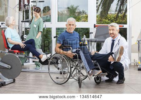Doctor Holding Senior Man's Leg In Wheelchair At Fitness Center