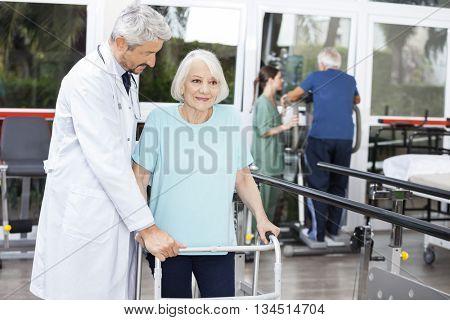 Doctor Assisting Senior Patient With Walker In Fitness Studio