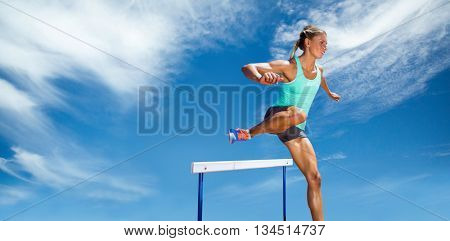 Sportswoman practising the hurdles against view of a blue sky