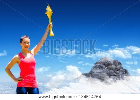 Sporty woman posing and smiling with Olympic torch against mountain peak through clouds
