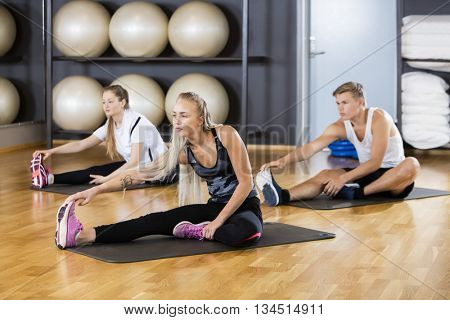 Friends Performing Stretching Exercise In Gymnasium