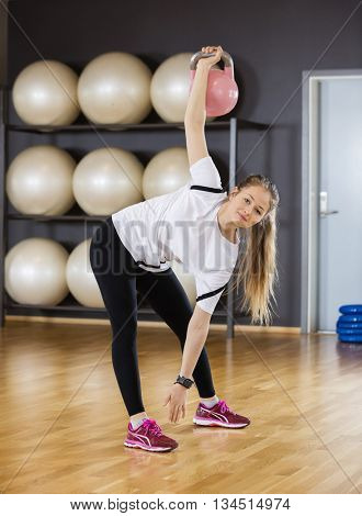 Portrait Of Woman Exercising While Lifting Kettlebell At Gym
