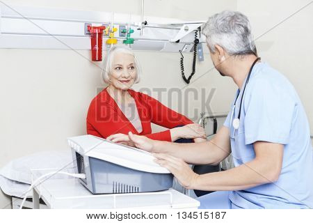 Senior Patient Looking At Male Physiotherapist Using Machine