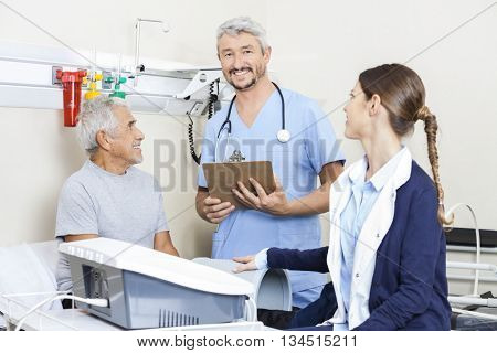 Male Physiotherapist With Colleague And Patient In Rehab Center