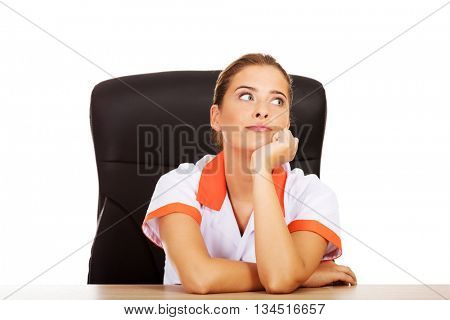 Tired young female doctoror nurse sitting behind the desk