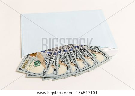Dollars in an envelope closeup on a white background