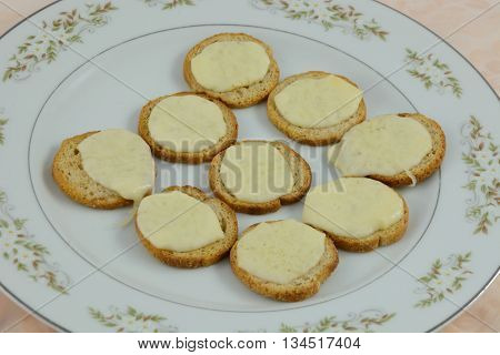 Appetizer snack plate of melba toast and melted mozzarella cheese