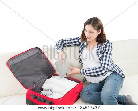 Attractive awaiting woman packing children's clothes into bag in order to go to maternity home.