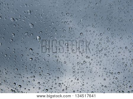 Raindrops on a window pane on the background of a stormy sky.