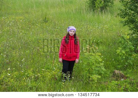 Teen girl in a red jacket walking in nature