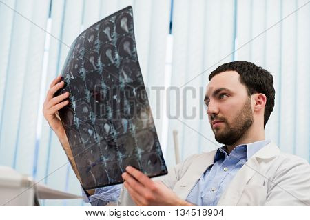 Closeup portrait of intellectual man healthcare personnel with white labcoat, looking at brain x-ray radiographic image, ct scan, mri, clinic office background. Radiology department.