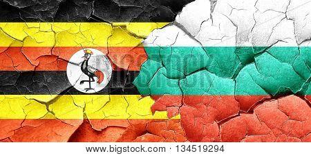 Uganda flag with Bulgaria flag on a grunge cracked wall