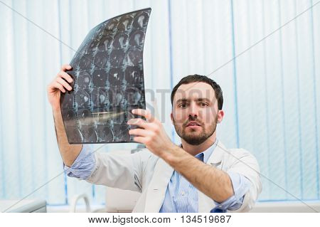Young doctor holding x-ray and looking worried.