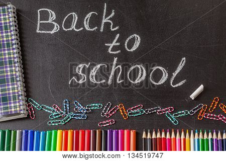 Back to school background with colorful felt tip pens pencils clips notebook and the title