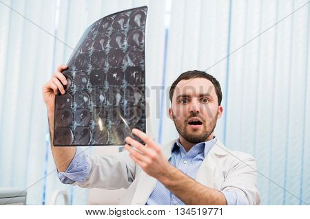 Shocked Young male Doctor Reviewing an MRI.