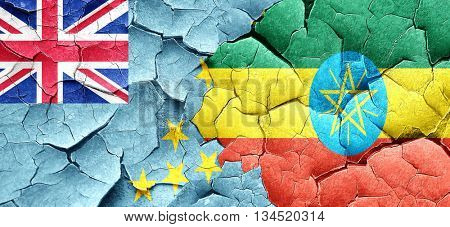 Tuvalu flag with Ethiopia flag on a grunge cracked wall