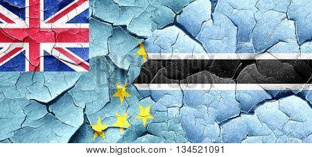 Tuvalu flag with Botswana flag on a grunge cracked wall