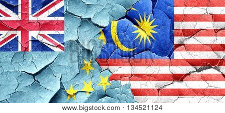 Tuvalu flag with Malaysia flag on a grunge cracked wall