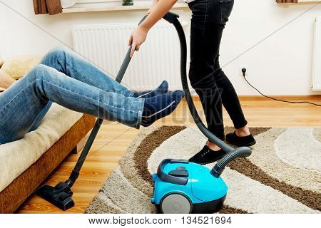 Woman vacuuming carpet man holding legs in the air