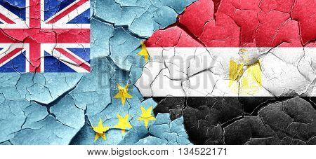 Tuvalu flag with egypt flag on a grunge cracked wall