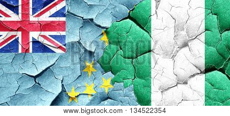 Tuvalu flag with Nigeria flag on a grunge cracked wall