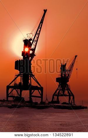 Silhouettes cranes freight ship on the shore of Lake Baikal in winter at sunset.