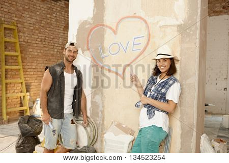 Young couple in new home under construction, standing by wall writing love and drawing heart on it, smiling happy.