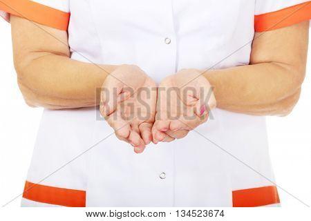 Elderly female doctor or nurse presenting something on open palms