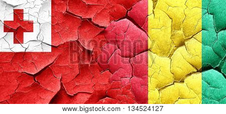 Tonga flag with Guinea flag on a grunge cracked wall