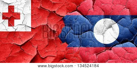 Tonga flag with Laos flag on a grunge cracked wall