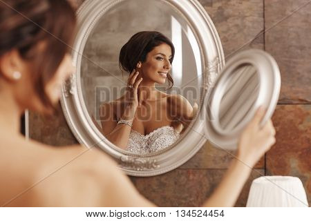 Beautiful young bride preparing herself in mirror.