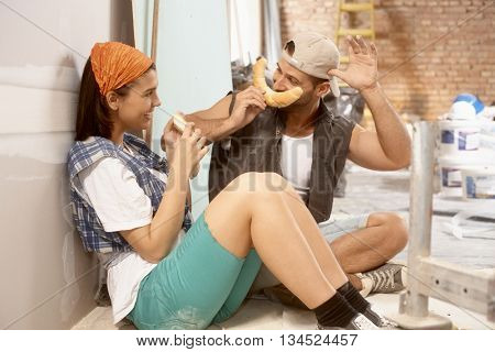 Young couple having fun with crescent rolls at home renovation.