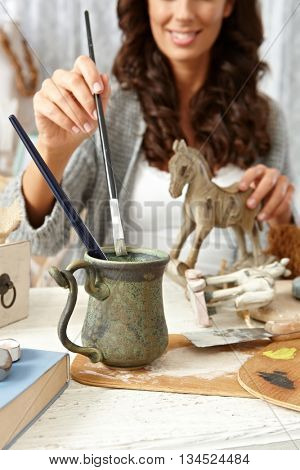Happy woman painting wooden horse at home in vintage style.