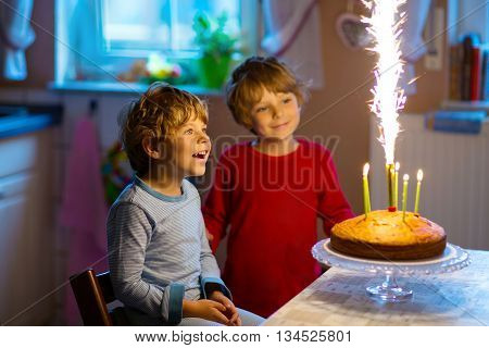 Beautiful kids, little boys celebrating birthday and blowing candles on homemade baked cake, indoor. Birthday party for children. Happy siblings about fireworks