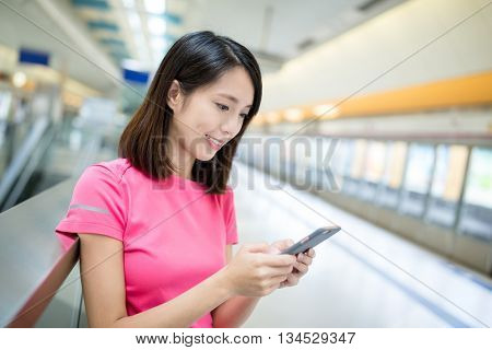 Woman use of smart phone at train station