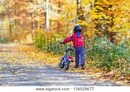 Little kid boy of four years in autumn forest with a bicycle. Active child wearing bike helmet. Safety, sports, leisure with kids concept.
