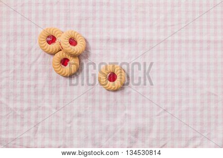 Sweet biscuit with strawberry jam at top on pink tablecloth background