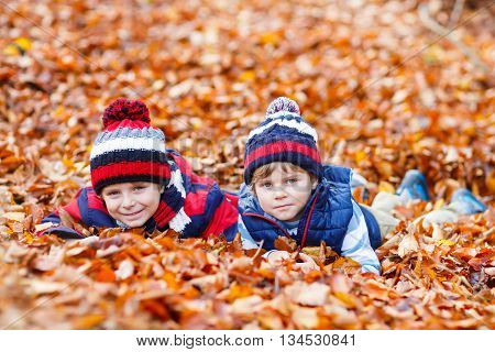 Two little brothers boys lying in autumn leaves in colorful clothing. Happy siblings kids having fun in autumn forest or park on warm fall day. With hats and scarfs