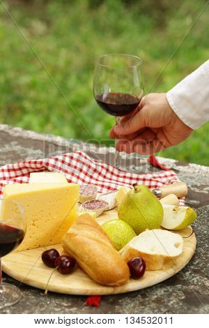 cheeseboard with pears and wine on a table in the garden
