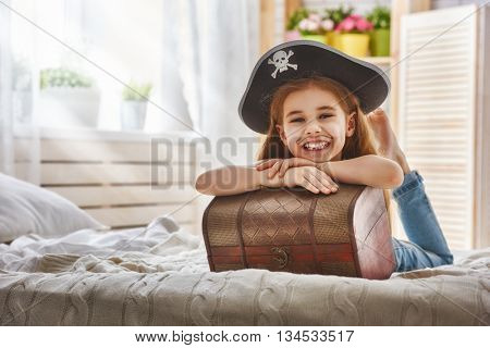 Cute little child girl in a pirate costume. Pretty child preparing for a costume party.