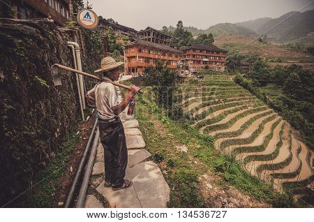 Guilin China - June 15 2014 : A worker or farmer looking at the view of his hard work. The shot was taken at Guilin China where the locals here at Longji Paddy Terrace live a simple life by growing and farming their own food.