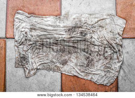 Dirty doormat lies on the pavement slab closeup
