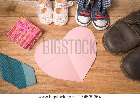 Daddy's Boots ,baby's Shoes ,textile Hearts ,gift  And  Blue Necktie On Wooden Background .fathers D
