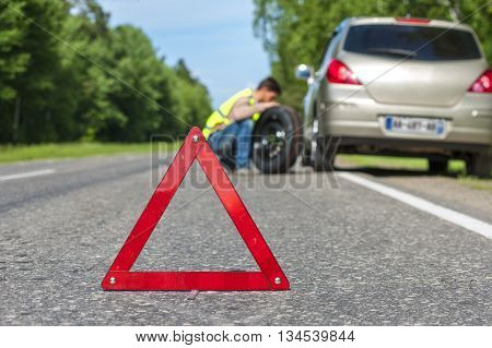 Male driver in reflective vest with spare wheel on the roadside broken car and red triangle warning sign. Focus on red sign