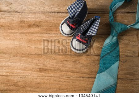 Fathers Day Composition Of Colorful Tie Laid And Baby Shoes On Wooden Background