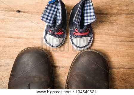 Daddy's Boots And Baby's Sneakers, On Wood Background, Fathers Day Concept.
