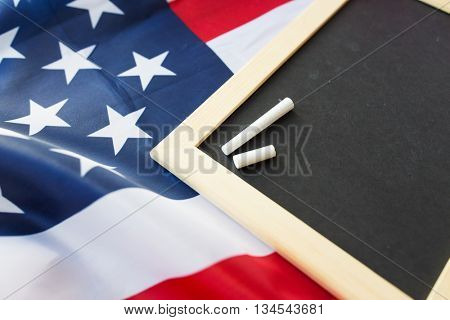 education, election, patriotism and nationalism concept - close up of blank school blackboard and chalk on american flag