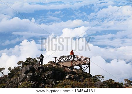 MOUNT KINABALU, SABAH BORNEO MALAYSIA - JUNE 12, 2016: Unidentified hikers having rest and enjoying the view of Ranau at the balcony of Mount Kinabalu new route trail.