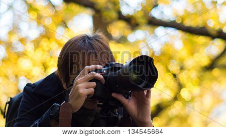 Asian adult man using profesional camera taking photograph