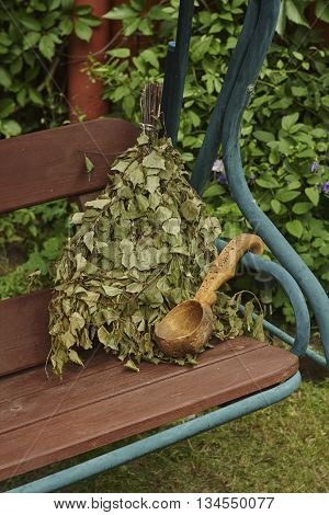 bunch of green birch twigs and scoop on bench close up